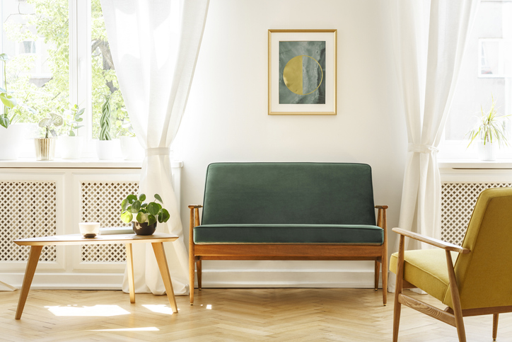 A mid-century living room interior with a sofa, coffee table, windows and painting